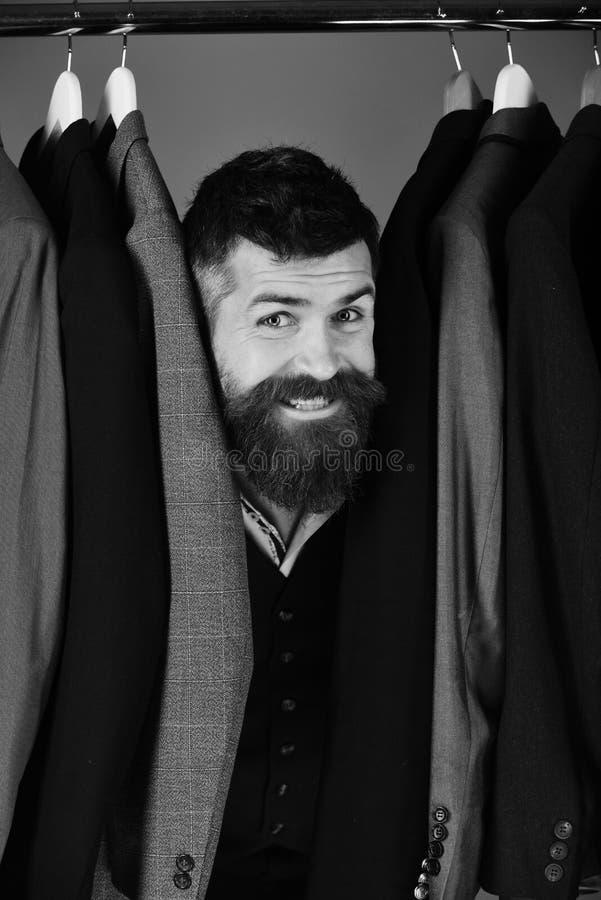 Manier en individueel stijlconcept Kleermaker met gelukkig gezicht dichtbij douanejasjes op blauwe achtergrond royalty-vrije stock fotografie