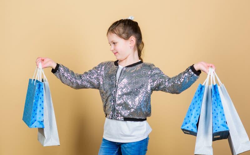 Manier en Stijl klant met pakket Verkoop en Kortingen Klein meisje met het winkelen zakken Vrolijk kind weinig stock foto's