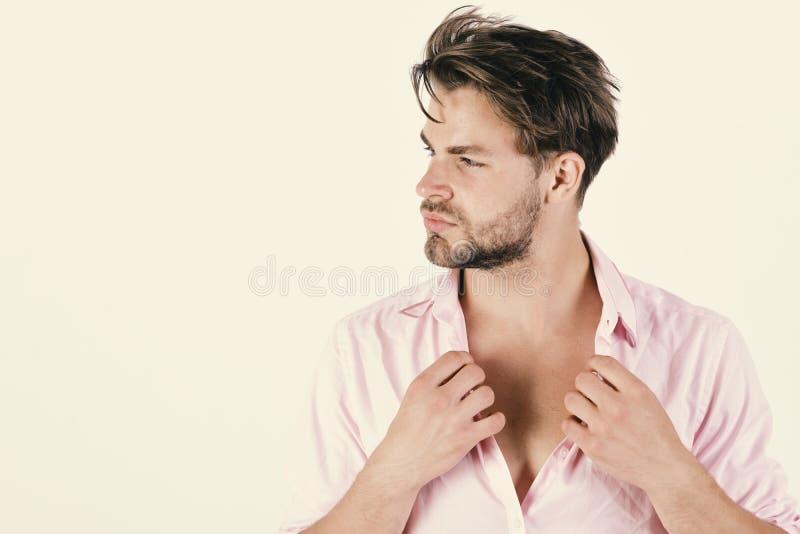 Manier en vertrouwensconcept De macho maakt knoop los opzij kijkend Kerel met varkenshaar in roze overhemd en slordig haar royalty-vrije stock fotografie