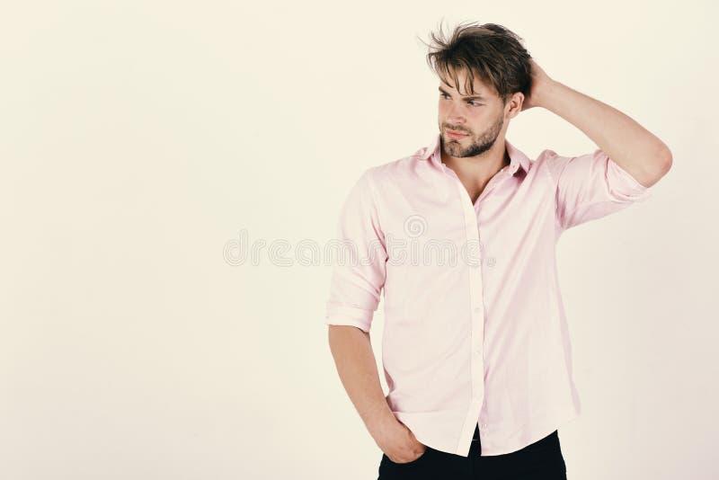 Manier en vertrouwensconcept De macho met sterke spieren wrijft zijn hoofd Kerel met varkenshaar in roze overhemd en slordig haar stock afbeeldingen