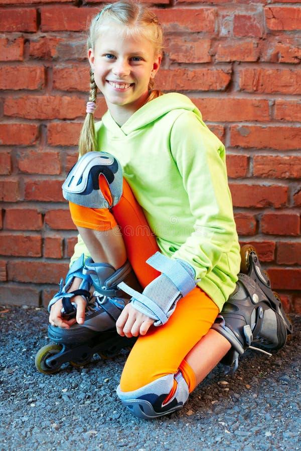 Manier gelukkig glimlachend hipster koel meisje in kleurrijke kleren met rolschaatsen die pret hebben in openlucht stock foto