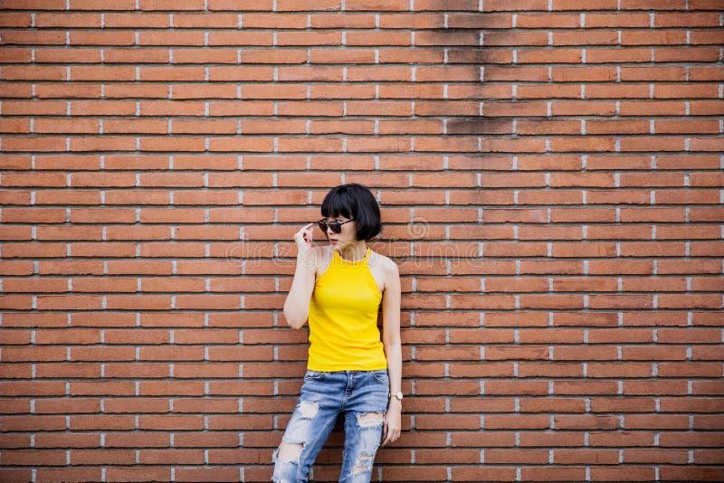 Manier gelukkig glimlachend hipster koel meisje in zonnebril die bij stedelijke bakstenen muurachtergrond stellen stock afbeelding