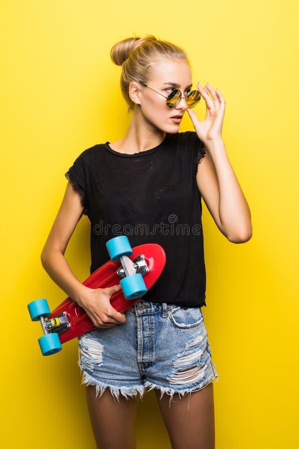 Manier gelukkig glimlachend hipster koel meisje in zonnebril met skateboard die pret hebben in openlucht tegen de gele achtergron royalty-vrije stock afbeeldingen