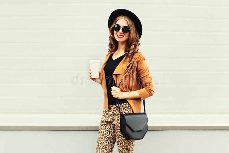 Manier gelukkige jonge glimlachende vrouw met koffiekop die een retro elegante hoed, een zonnebril, een bruin jasje en een zwarte royalty-vrije stock afbeelding