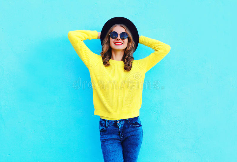 Manier gelukkige mooie glimlachende vrouw die een zwarte hoed en een gele gebreide sweater over kleurrijk blauw dragen royalty-vrije stock foto's