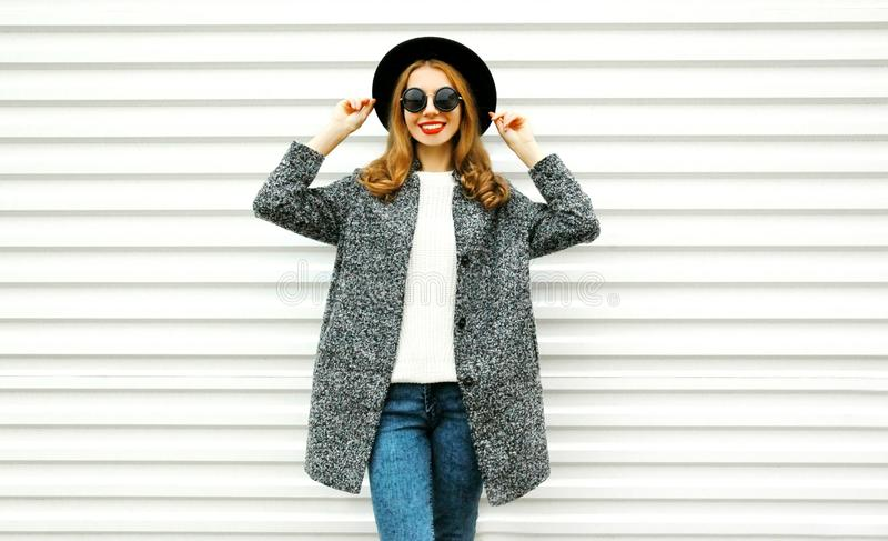 Manier glimlachende vrouw in grijze laag, het zwarte ronde hoed stellen stock foto's