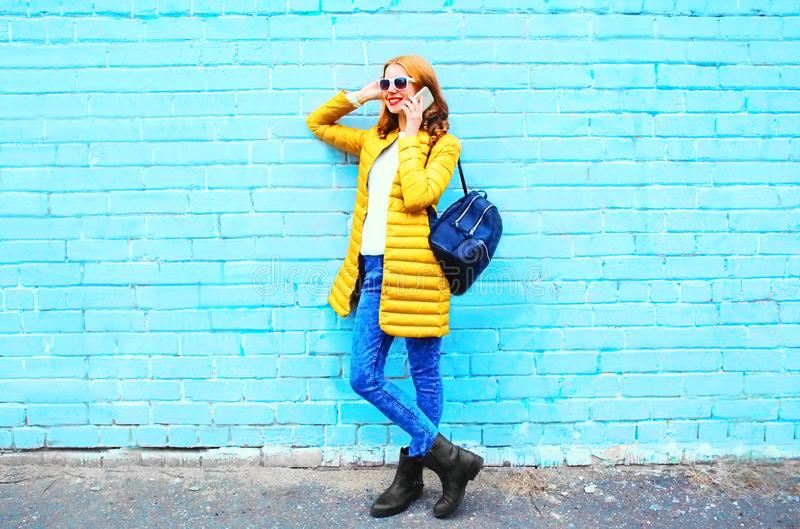Manier het glimlachen vrouwenbesprekingen op een smartphone op een blauwe baksteen stock afbeelding