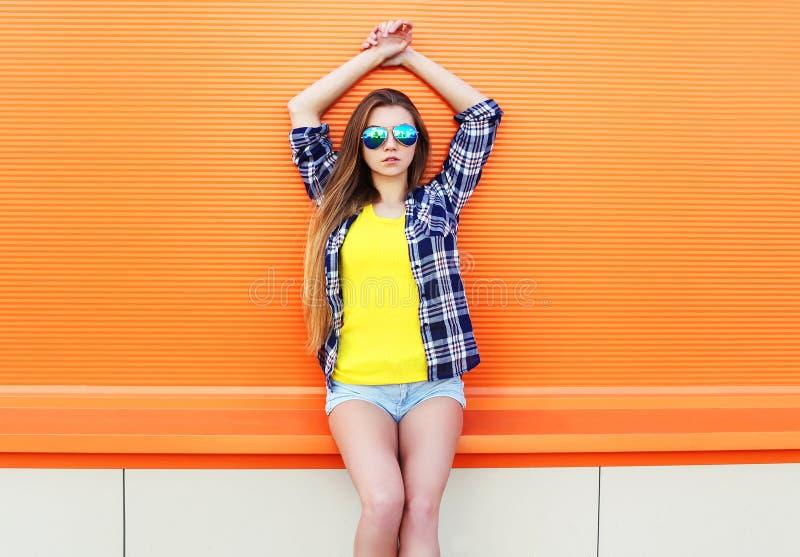 Manier het mooie meisje dragen zonnebril en borrels in stad over kleurrijk stock foto