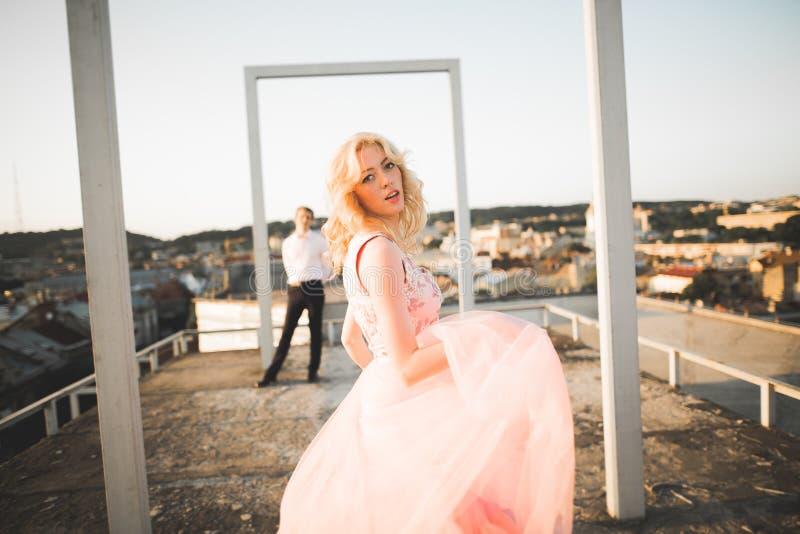 Manier het mooie mooie paar stellen op dak met stadsachtergrond Jonge mens en sensueel blonde openlucht levensstijl stock afbeeldingen