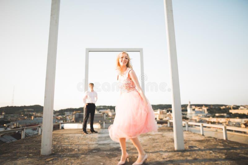Manier het mooie mooie paar stellen op dak met stadsachtergrond Jonge mens en sensueel blonde openlucht levensstijl royalty-vrije stock foto's