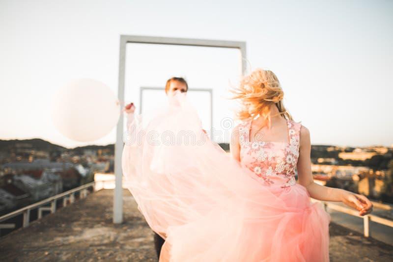 Manier het mooie mooie paar stellen op dak met stadsachtergrond Jonge mens en sensueel blonde openlucht levensstijl royalty-vrije stock foto