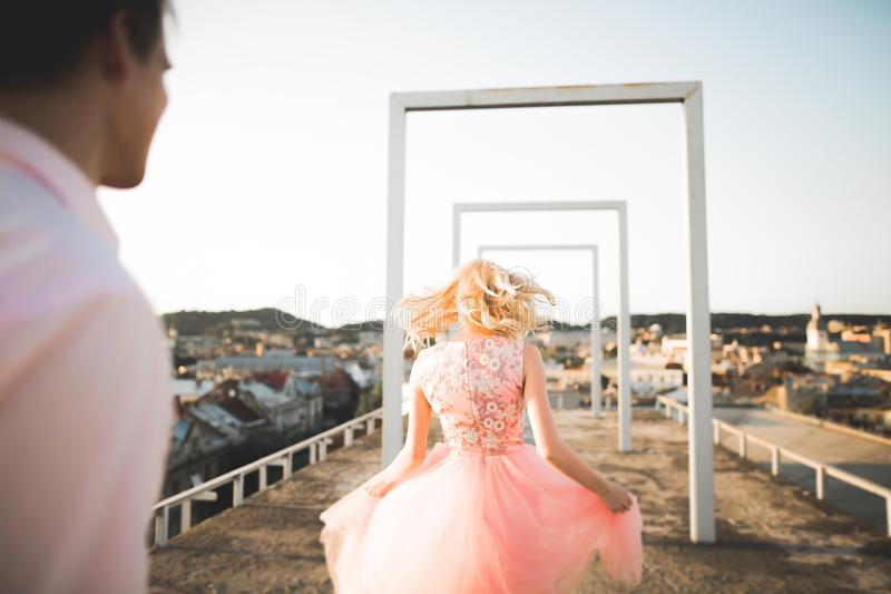 Manier het mooie mooie paar stellen op dak met stadsachtergrond Jonge mens en sensueel blonde openlucht levensstijl royalty-vrije stock fotografie