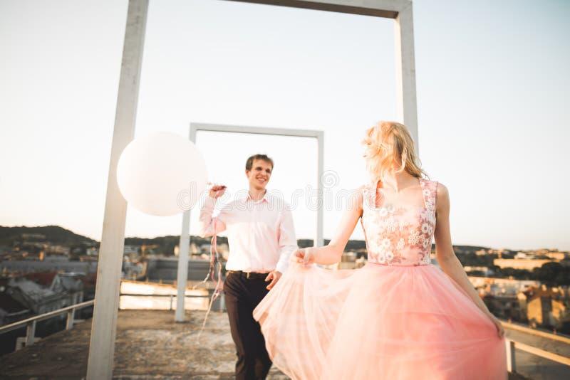 Manier het mooie mooie paar stellen op dak met stadsachtergrond Jonge mens en sensueel blonde openlucht levensstijl stock fotografie