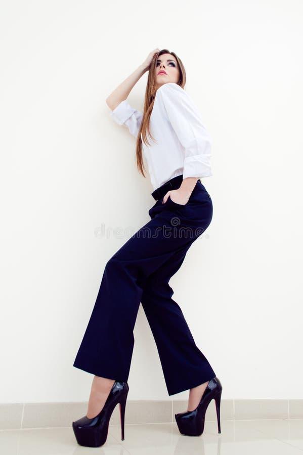 Manier jonge bedrijfsvrouw die man overhemd op wit dragen stock foto