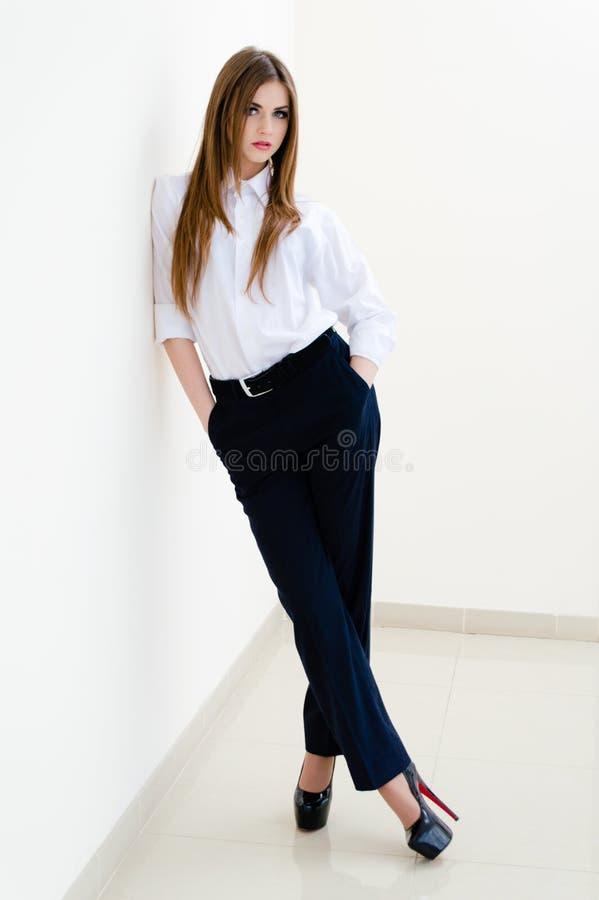 Manier jonge bedrijfsvrouw die man overhemd op wit dragen stock afbeeldingen