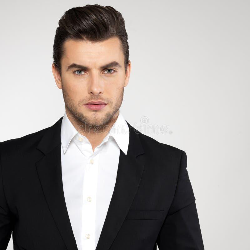 Manier jonge zakenman in zwart kostuum stock afbeelding