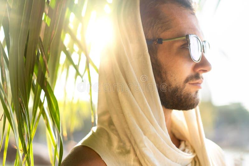 Manier knappe kerel bij zonsondergang het stellen in een witte robe dichtbij de rotsen stock foto's