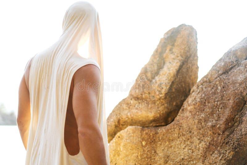Manier knappe kerel bij zonsondergang het stellen in een witte robe dichtbij de rotsen royalty-vrije stock afbeelding
