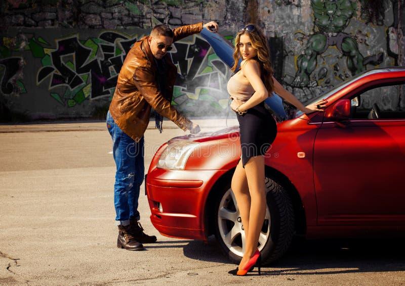 Manier mannelijke model reparing auto voor wellustig blonde jonge woma stock foto