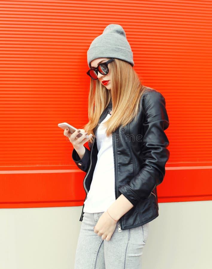 Manier modieuze jonge vrouw die smartphone gebruiken die in stad lopen stock foto's
