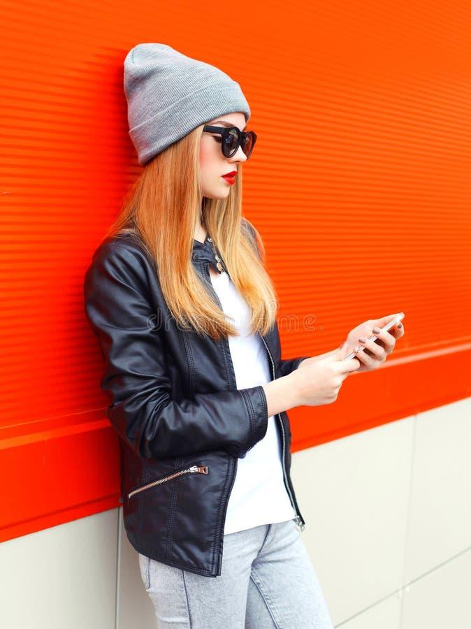 Manier modieuze jonge vrouw die smartphone in stad over rood gebruiken stock foto's