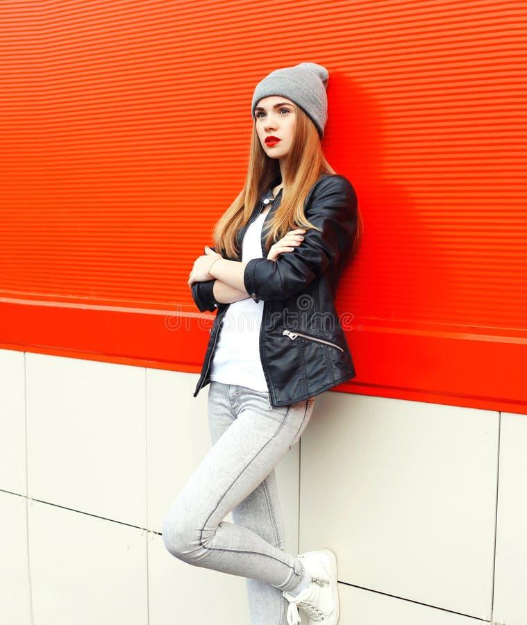Manier modieuze mooie vrouw die een rots zwarte jasje en een hoed over rood dragen stock fotografie