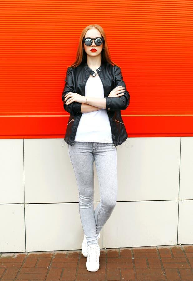 Manier modieuze vrouw die een rots zwart jasje en zonnebril in stad over rood dragen stock foto