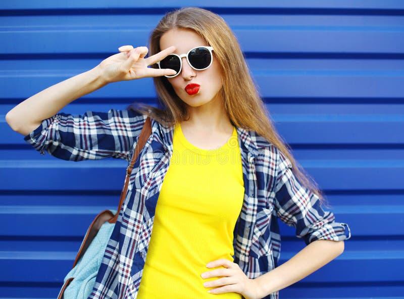 Manier mooi meisje die kleurrijke kleren dragen die pret over blauw hebben stock foto's