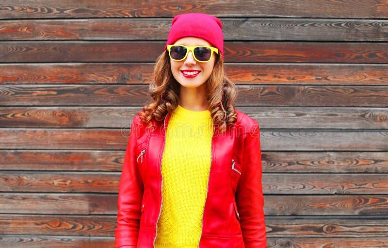 Manier mooie glimlachende vrouw die een rode hoed van het leerjasje in de herfst over houten dragen royalty-vrije stock fotografie