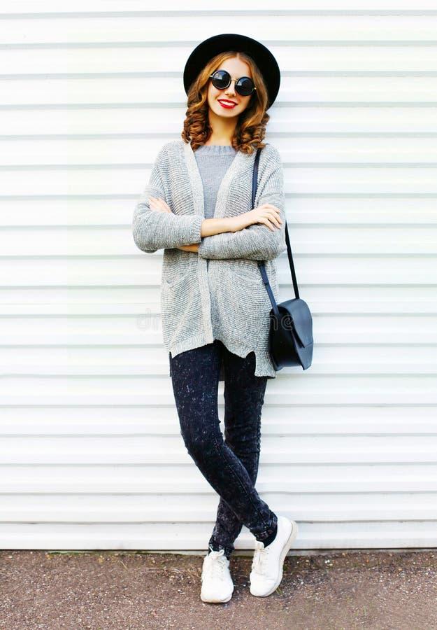 Manier mooie glimlachende vrouw met een zwarte handtas op een wit stock fotografie