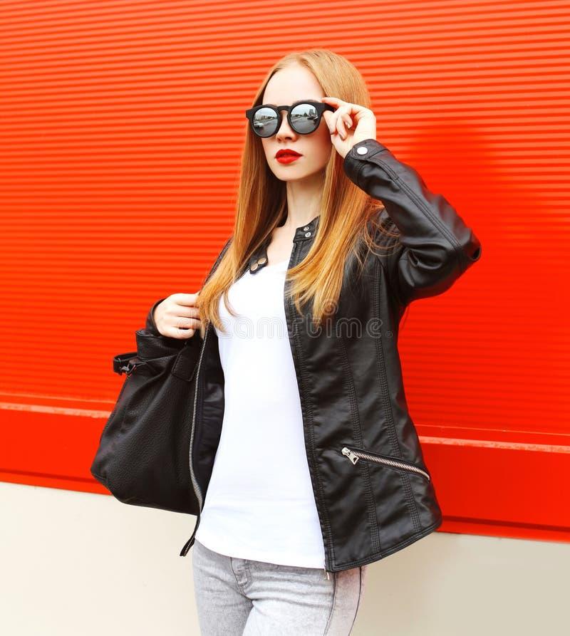 Manier mooie vrouw die een rots zwart jasje, zonnebril en zak over rood dragen stock afbeeldingen