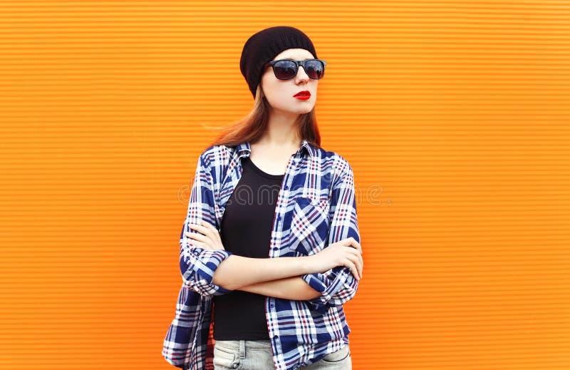 Manier mooie vrouw die een zwarte hoed, een zonnebril en een geruit overhemd over kleurrijk dragen royalty-vrije stock foto's