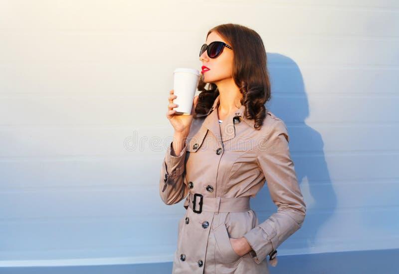 Manier mooie vrouw die met koffiekop van smaak genieten die in stadsavond lopen stock fotografie