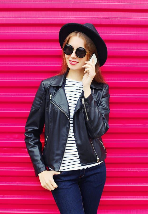 Manier mooie vrouw die op smartphone in rots zwarte stijl spreken over kleurrijk roze stock afbeeldingen