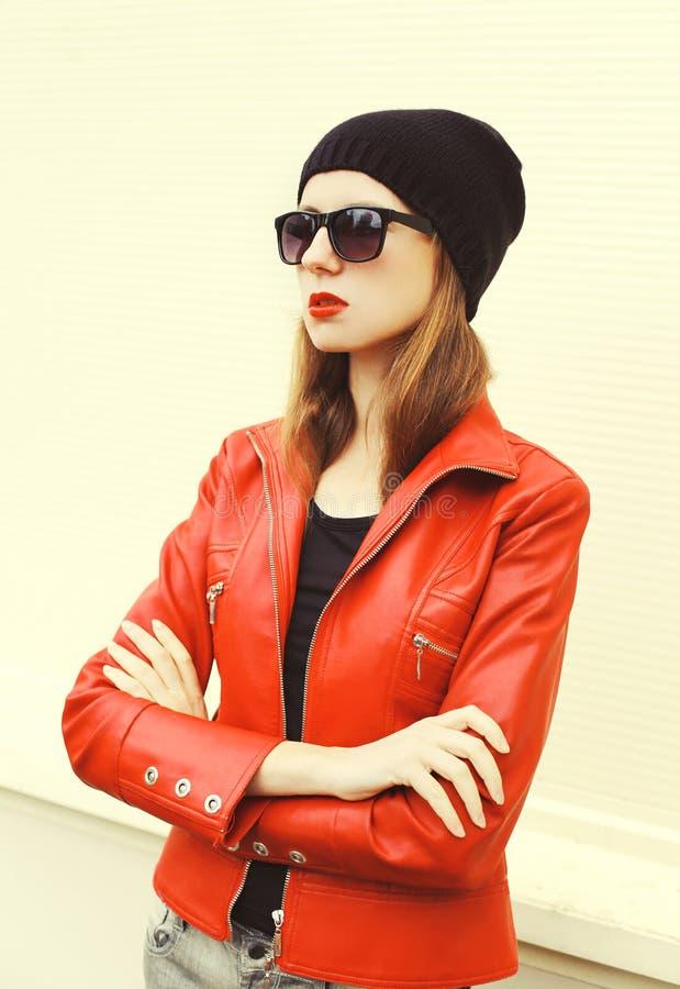 Manier mooie vrouw met rode lippenstift die een jasje van het rotsleer, een zonnebril en een zwarte hoed dragen stock fotografie