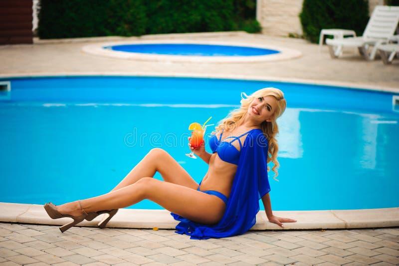 Manier openluchtfoto die van mooie sensuele vrouw die elegante bikini dragen, naast zwembad met cocktail stellen stock foto's