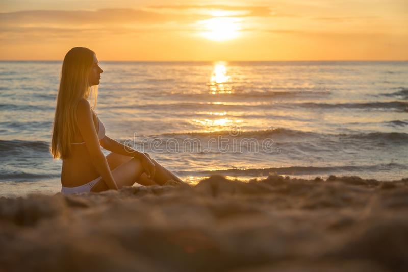 Manier openluchtfoto van sexy mooi meisje met blondehaar in het elegante witte bikini ontspannen op zonsondergangstrand royalty-vrije stock foto