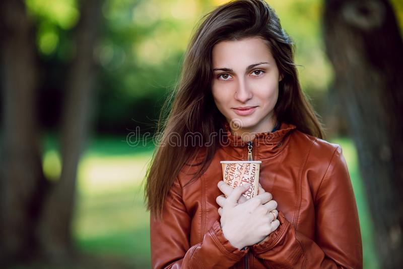 Manier openluchtportret van schitterende lange haarvrouw in bruin leerjasje met kop van coffe Modieus meisje in in kleren stock foto