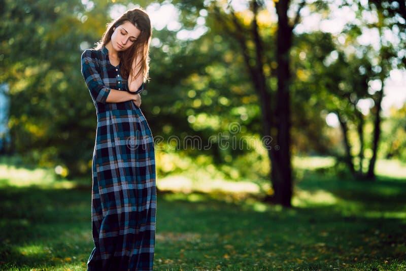 Manier openluchtportret van schitterende lange haarvrouw in lange geruite blauwe kleding - spring stijl op Modieus jong meisje in royalty-vrije stock afbeelding