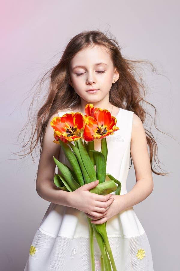 Manier roodharig meisje met tulpen in handen Studiofoto op licht gekleurde achtergrond Verjaardag, vakantie, moeder` s dag, eerst stock afbeelding