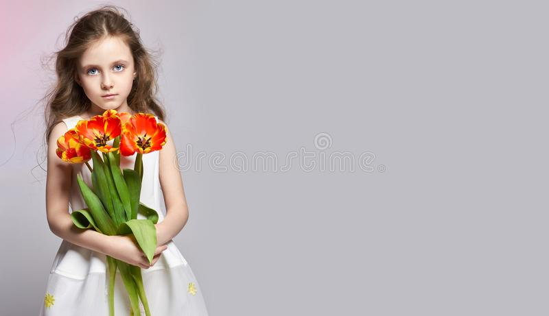 Manier roodharig meisje met tulpen in handen Studiofoto op licht gekleurde achtergrond Verjaardag, vakantie, moedersdag, eerste d royalty-vrije stock afbeeldingen