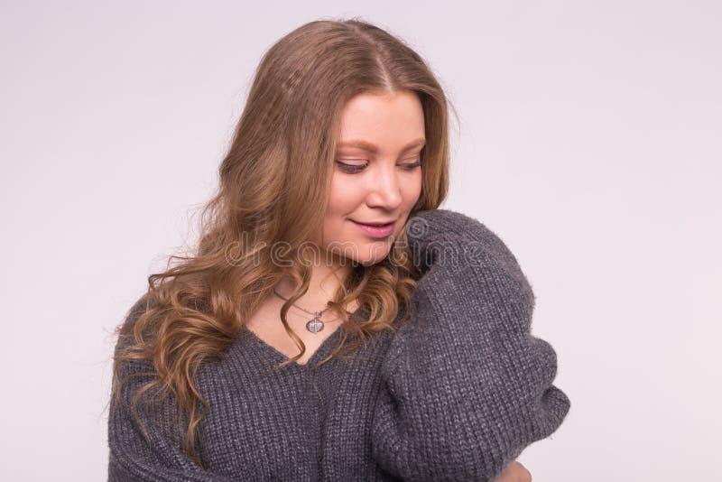 Manier, stijl en mensenconcept - portret van een mooie jonge vrouw met een zachte glimlach over witte achtergrond stock afbeelding