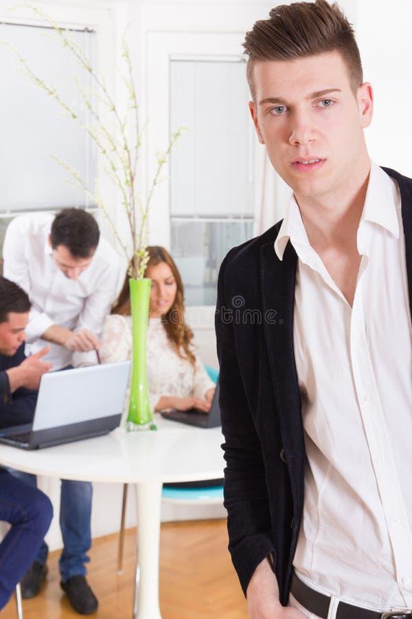 Manier toevallige mens in een bedrijfsatmosfeer met collega'sbehi stock afbeelding