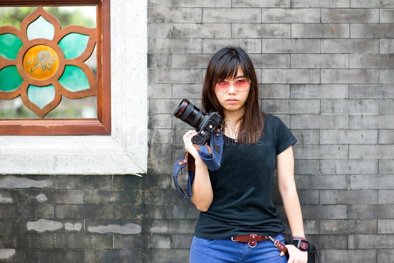 Manier van een meisje die een gestreepte holding dragen de camera stock afbeelding
