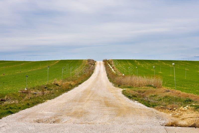 manier van zand aan de horizon met landbouwgebieden van groene gewassen aan beide kanten van de manier met irrigatiesystemen en b royalty-vrije stock fotografie