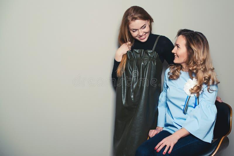 Manier, verkoop en levensstijlconcept Gelukkige en vrouwen die spreken lachen Opgewekte modieuze jonge vrouwen die pret hebben sa stock foto
