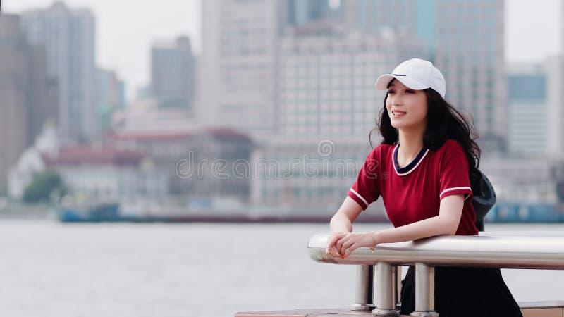 Manier vrij jong meisje met zwart lang haar, die rode T-shirt en wit honkbal GLB dragen die openlucht, minimalistische stedelijke royalty-vrije stock foto's