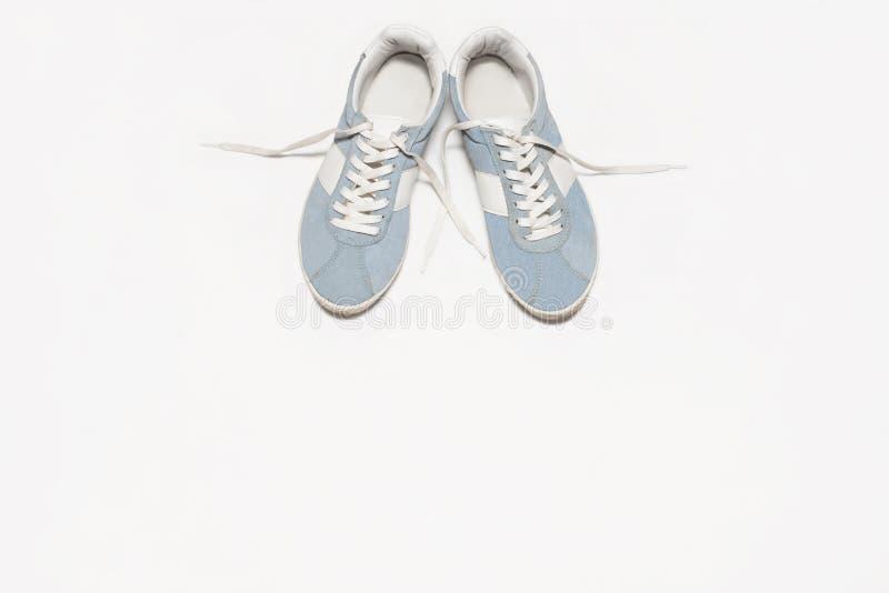 Manierblog Blauwe vrouwelijke tennisschoenen op witte achtergrond Vlak leg, hoogste mening stock afbeelding