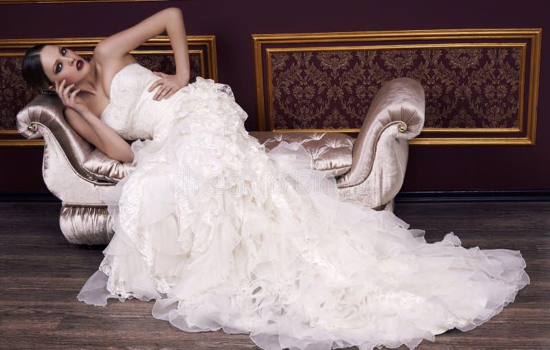 Manierbruid met blond haar in het luxueuze kleding stellen in binnenland stock fotografie