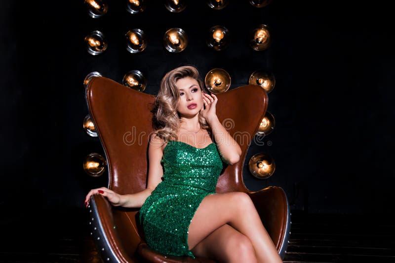Manierfoto die van een mooie jonge vrouw in elegante korte kleding, op een stoel op een zwarte donkere achtergrond met lampen zit royalty-vrije stock foto's